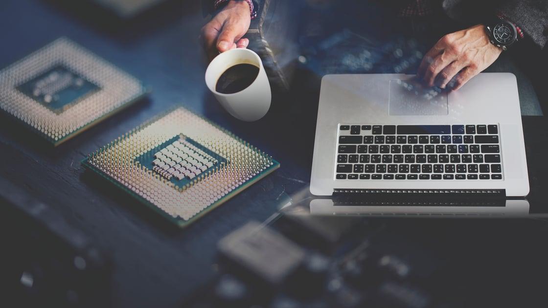 Departamento de Soporte IT interno. Un hombre con una Macbook y una taza de café resuelve problemas de tecnología sobre lo que parece ser una placa de circuitos.