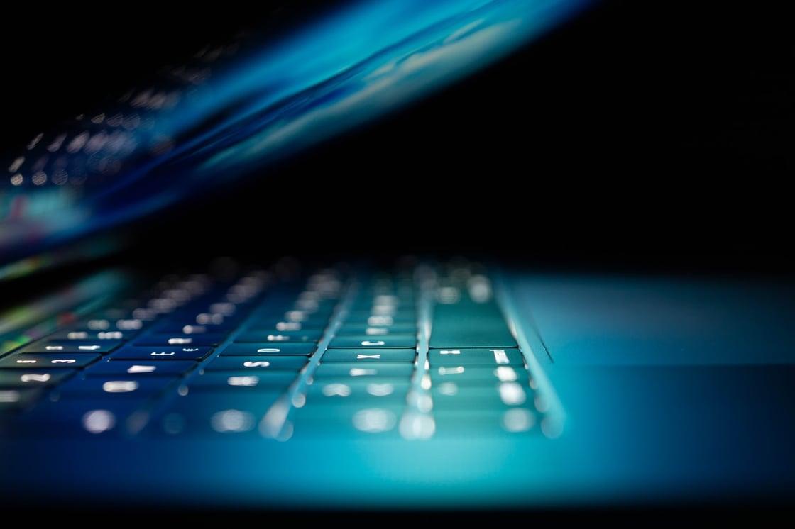 Laptop semi abierta en una habitación oscura. La protección endpoint resulta fundamental para preservar la seguridad de los dispositivos de red